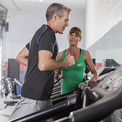 man running on treadmill with a personal trainer checking form