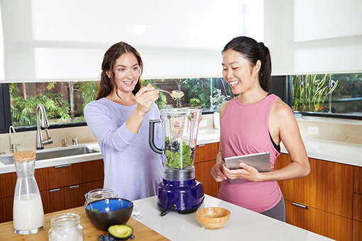 two trainers making healthy smoothies in a kitchen