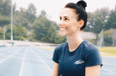 Personal trainer smiling outdoors.