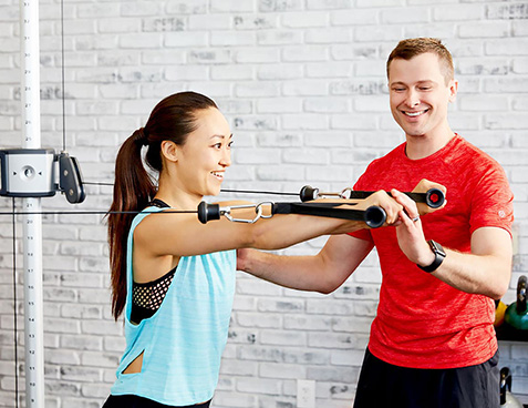 personal trainer training a client with strength endurance cable exercises