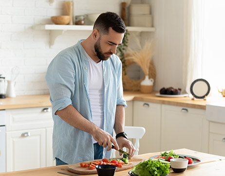 a man preparing vegetables in a kitchen after calculating calories